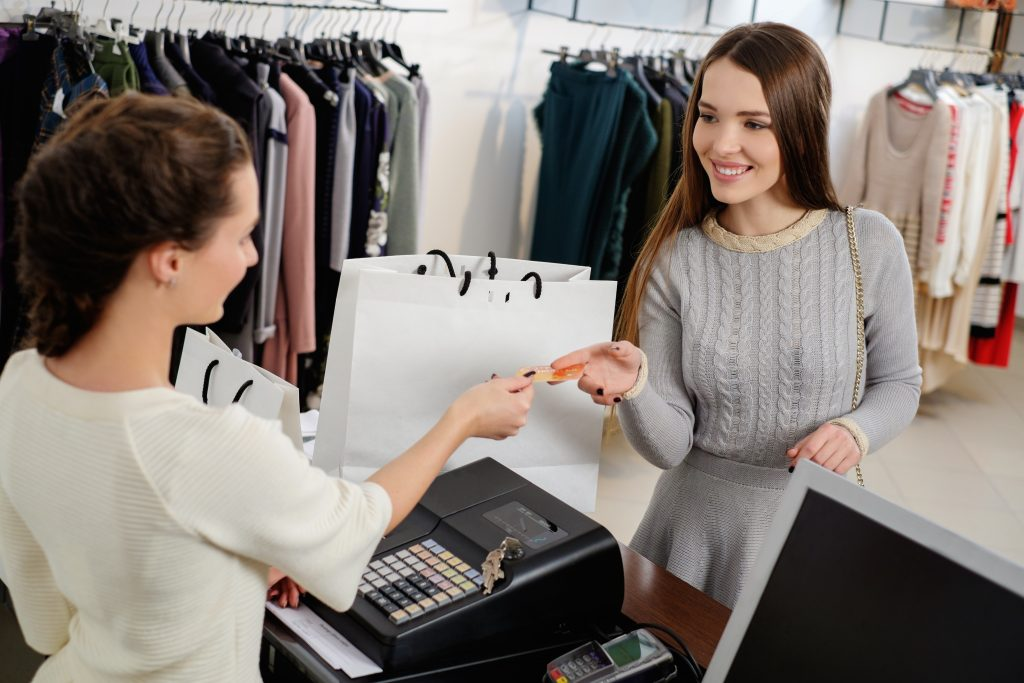 TVFCU Happy woman customer paying with credit card in fashion showroom